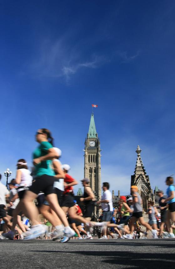 Joggers running past parliament buildings ottawa